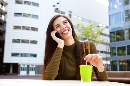 handphone: Portrait of smiling woman talking with cellphone at cafe