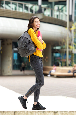 Portrait of smiling female college student walking to class with bag
