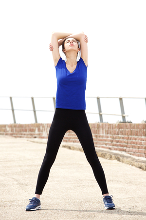 arms above head: Full length portrait of sporty young woman stretching arms above head Stock Photo