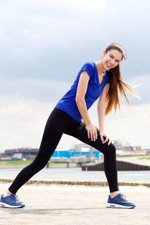 stretch: Full length portrait of a smiling young sporty woman stretching outside Stock Photo