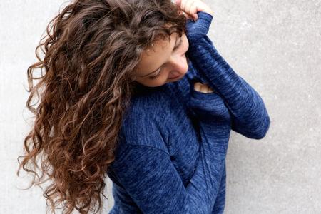cabello rizado: Cerca de retrato de mujer joven con el pelo largo sonriendo contra la pared gris