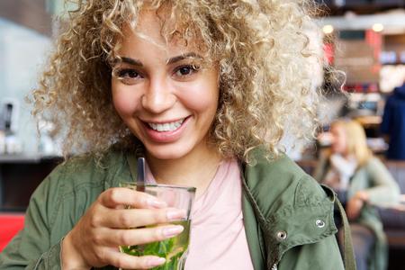 menta: Cerca de retrato de la mujer sonriente con vaso de té de menta