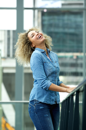 head back: Portrait of laughing woman with head back and hands on railing