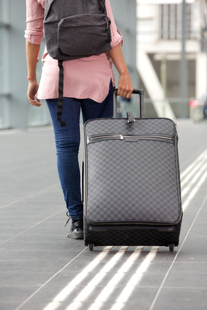 Portrait from behind of young female traveler walking away with suitcase