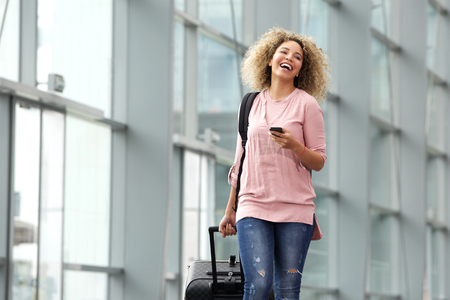 cellphones: Portrait of female traveler holding cellphone and suitcase