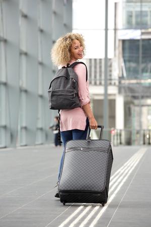 Full length portrait of female traveler looking over shoulder
