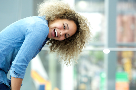 attitudes: Close up side portrait of a young african american woman laughing Stock Photo
