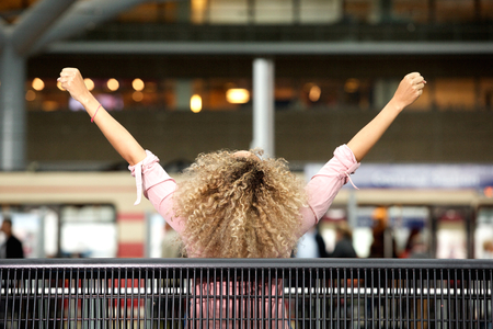 hair back: Portrait from behind of carefree woman with arms outstretched Stock Photo