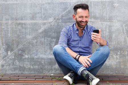 sidewalk: Portrait of happy mature man sitting outdoors against a wall and reading text message on his mobile phone Stock Photo