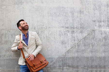 Portrait of handsome middle aged guy standing against wall looking away at copy space and smiling