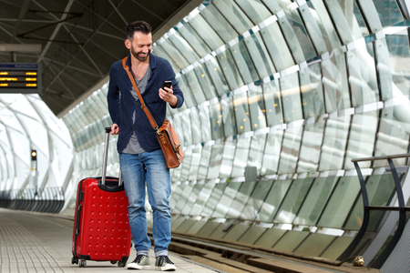 cuerpo hombre: Full length portrait of mature guy walking with suitcase and looking at mobile phone on railway platform Foto de archivo