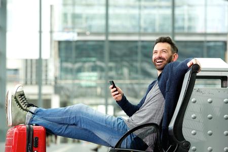 Retrato de hombre maduro feliz sentado con bolsa de viaje y el teléfono móvil en la estación de tren