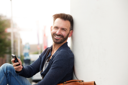 man sit: Close up portrait of handsome man with cell phone sitting by a wall outdoors and smiling
