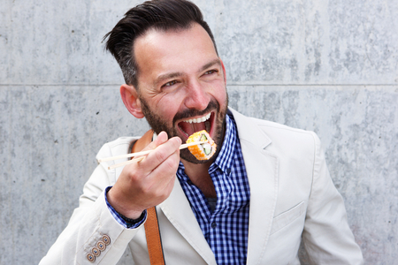 Close up portrait of happy mature man eating sushi with chopsticks