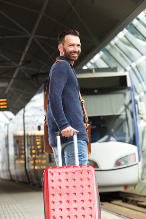 waiting glance: Portrait of middle aged man standing on railway platform with suitcase