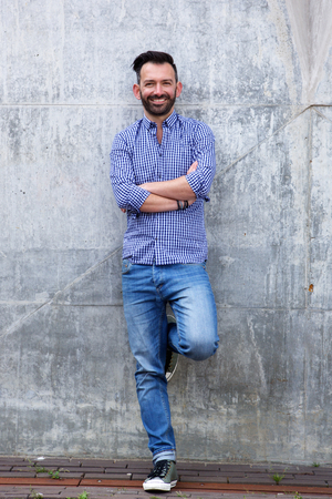 leaning: Full length portrait of confident mature man standing against wall with arms crossed
