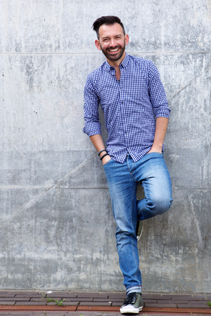 Full length portrait of happy mature male model posing against wall and smiling Stok Fotoğraf