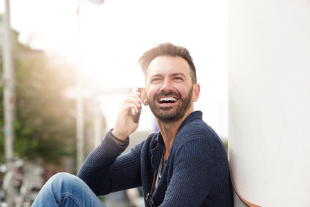 sidewalk talk: Close up portrait of mature guy sitting outdoors talking on mobile phone and laughing Stock Photo