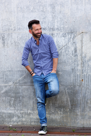 man shirt: Full length portrait of stylish mature man standing against wall and looking away