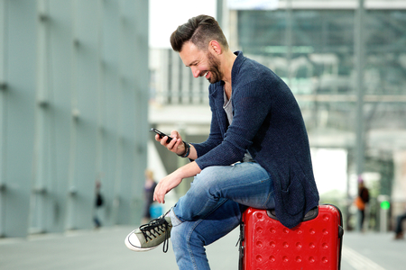 Side portrait of happy mature man sitting on traveling bag and looking at cell phone