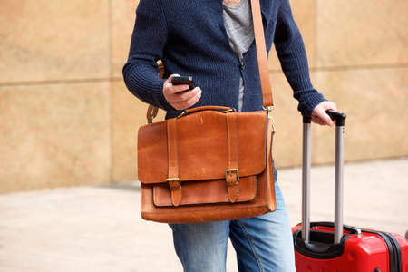 travel bag: Close up portrait of male traveler standing outdoors with cellphone and travel bag