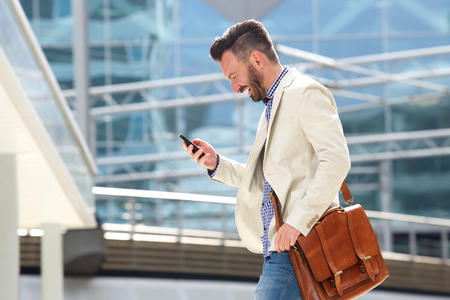 Side portrait of smiling mature man with bag walking outdoors and reading text message on his cell phone