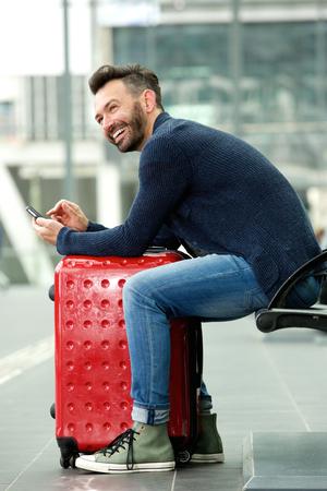 valise voyage: portrait de côté d'un homme souriant d'âge mûr assis à la gare avec un sac et un téléphone cellulaire Banque d'images