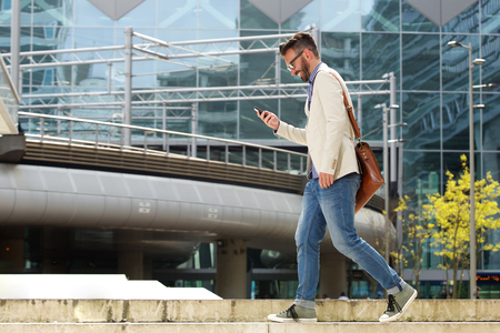 Full length side portrait of happy caucasian man walking outdoors and reading text message on his mobile phone