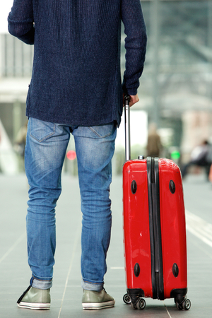back view: Rear portrait of man with traveling bag standing at train station