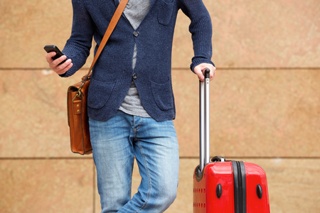 luggage travel: Cropped portrait of man standing outdoors with cellphone and travel bag