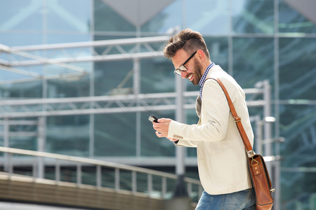 Side portrait of smiling mature businessman looking at mobile phone