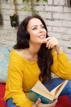 Portrait of attractive woman holding book and smiling