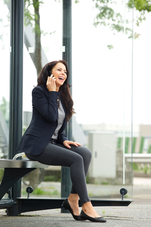 woman stop: Full body portrait of attractive business woman waiting at bus stop