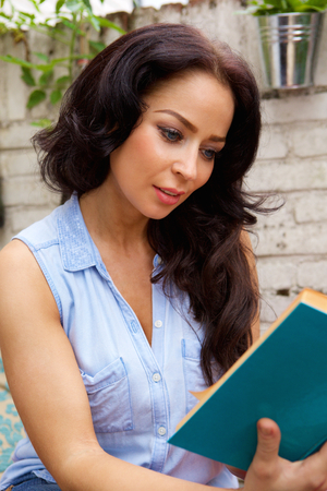 Portrait of attractive woman reading book outside Stock Photo