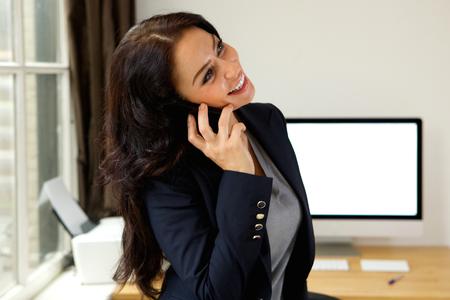 Retrato de mujer de negocios sonriente hablando por teléfono móvil en la oficina Foto de archivo - 63365221