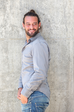 Portrait of smiling man with beard leaning against wall