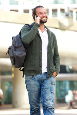 cool guy: Portrait of cool guy with beard smiling outside with mobile phone and bag