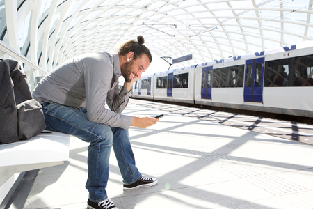 Portrait of smiling man sitting at train platform with cellphone