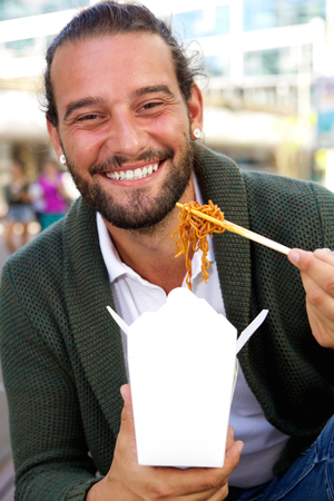 take out: Portrait of smiling man eating take out food with chopsticks