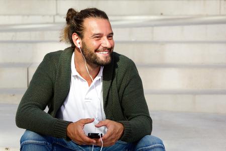 Ritratto di uomo attraente sorridente con smart phone e cuffie Archivio Fotografico