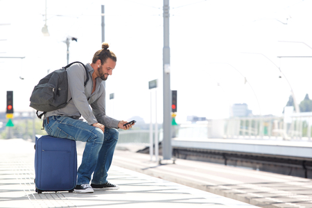 cool guy: Portrait of cool guy sitting on suitcase waiting for train