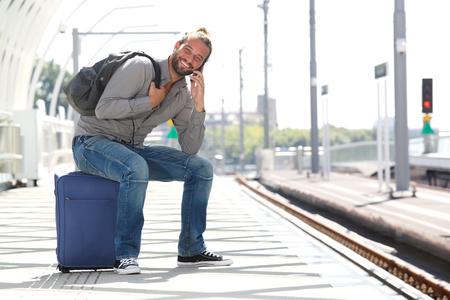 Portrait of man talking on phone waiting at train platform