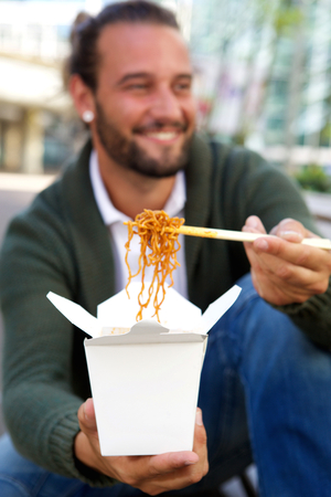 take out: Portrait of young man offering take out noodles chopsticks Stock Photo