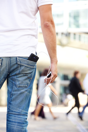charger: Portrait of man from behind holding cellphone with battery charger in pocket