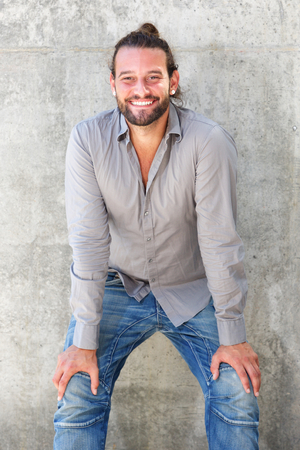 leaning forward: Portrait of smiling man leaning forward with hands on knees