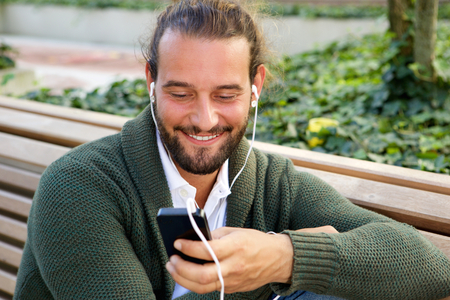 smile face: Portrait of happy man in sweater holding smart phone with earphones