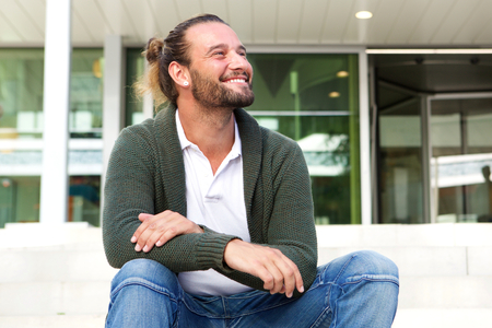 man with beard: Portrait of smiling man with beard sitting on steps looking away Stock Photo