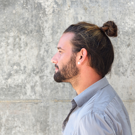 Close up side portrait of serious man with beard and hair bun