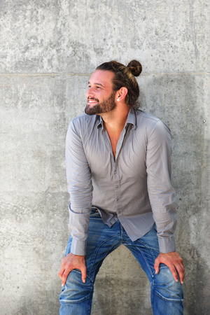 leaning forward: Portrait of smiling man with beard leaning forward with hands on knees Stock Photo