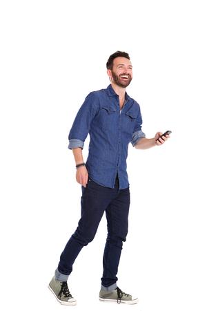 completo: Retrato de cuerpo entero del hombre maduro guapo que camina con el teléfono móvil y que ríe sobre el fondo blanco